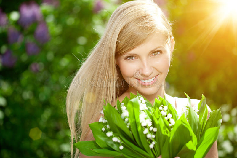 Mujer joven con una sonrisa hermosa con los dientes sanos con el flowe imagen de archivo libre de regalías