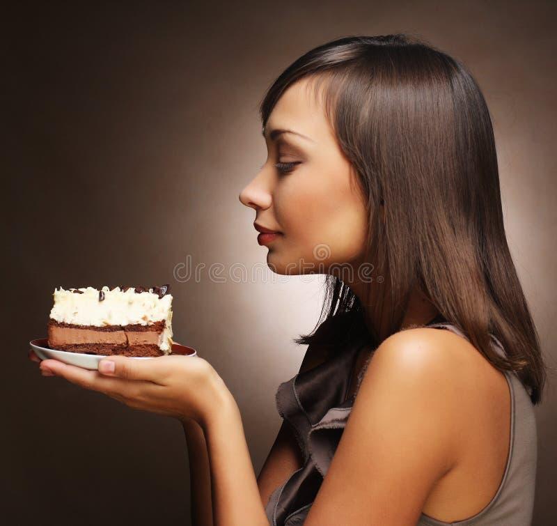 Mujer joven con una torta y un café foto de archivo libre de regalías