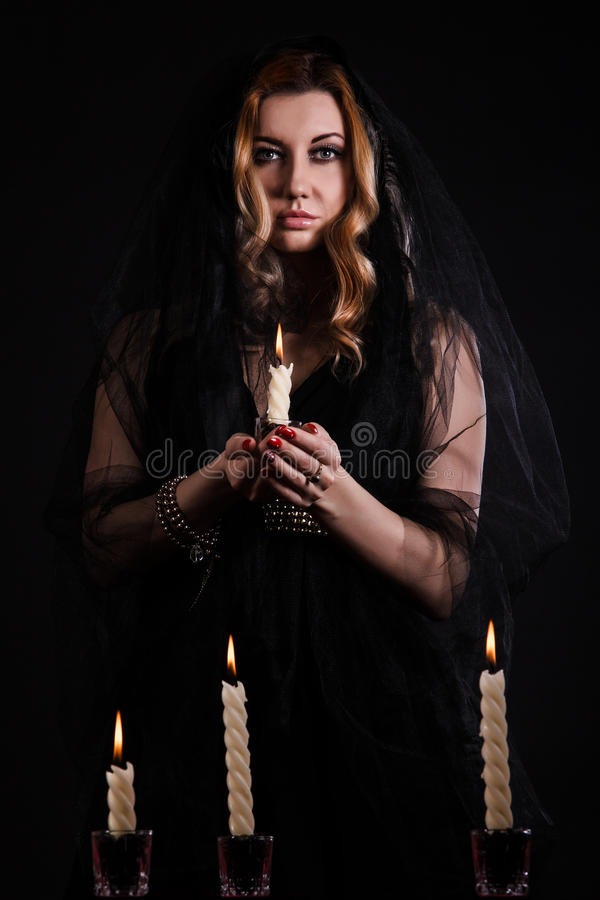 Mujer joven con una vela en oscuridad foto de archivo