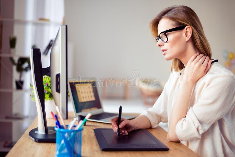 Mujer joven concentrada en vidrios que retoca la foto para un largo fotos de archivo libres de regalías