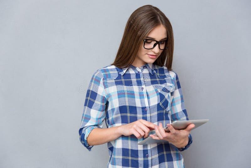 Mujer joven concentrada que usa la tableta fotos de archivo