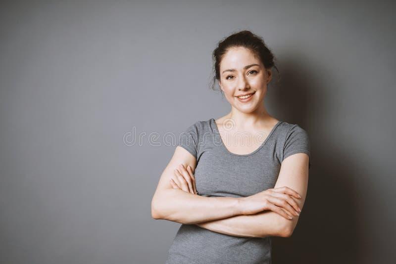 Mujer joven confiada con los brazos doblados imagen de archivo libre de regalías
