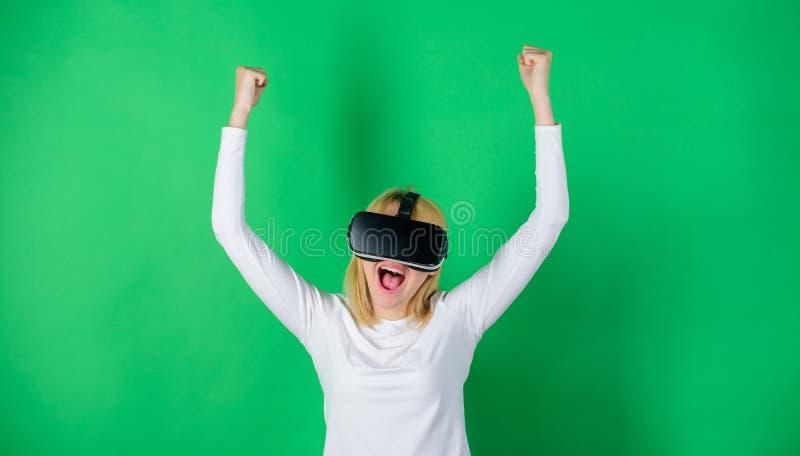 Mujer joven confiada que ajusta sus auriculares y sonrisa de la realidad virtual Mujer que usa el dispositivo de VR Realidad aume imagenes de archivo