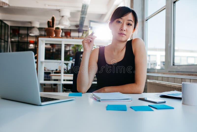 Mujer joven confiada que se sienta en su escritorio imagen de archivo