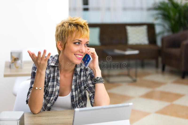 Mujer joven contenta que charla en su smartphone fotografía de archivo libre de regalías