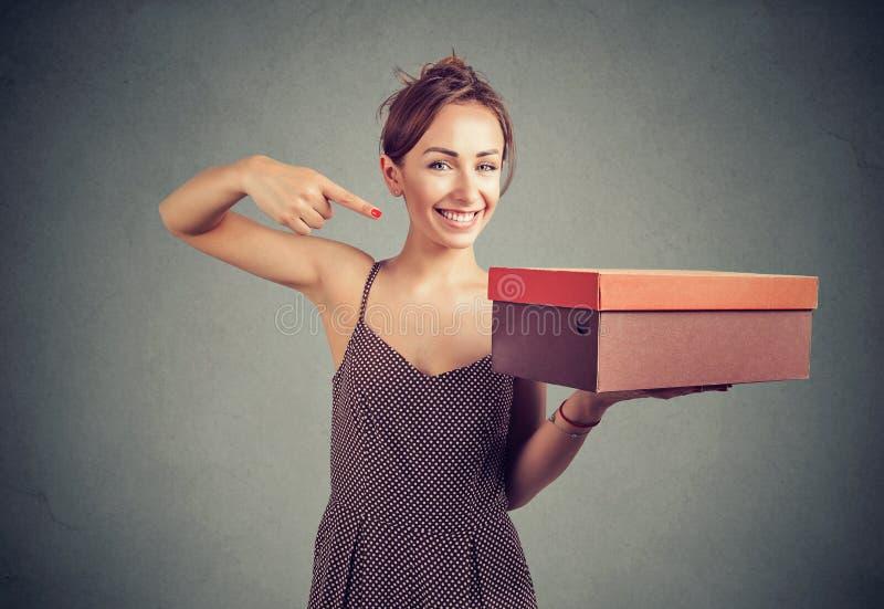 Mujer joven contenta que presenta la caja fotografía de archivo