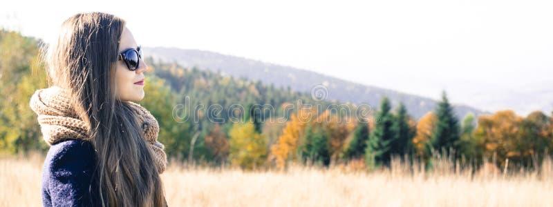 Mujer joven contra fondo del paisaje del otoño fotografía de archivo