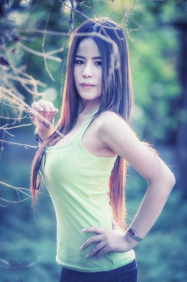 Mujer joven de Asia que lleva el chaleco verde en parque imagenes de archivo