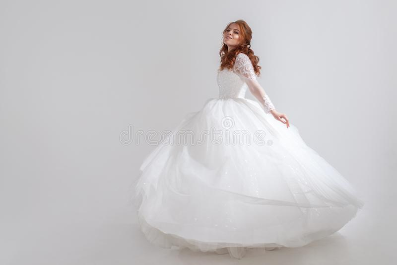Mujer joven de baile en vestido de boda Novia encantadora en fondo ligero fotografía de archivo libre de regalías