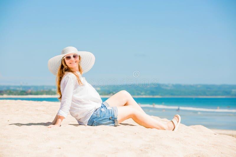Mujer joven de Beautifil que miente en la playa en soleado fotos de archivo