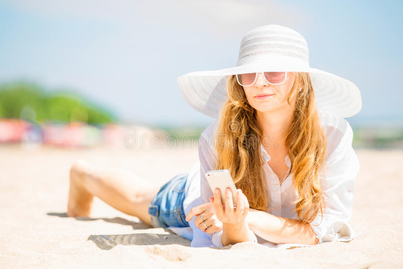 Mujer joven de Beautifil que miente en la playa en soleado fotos de archivo libres de regalías