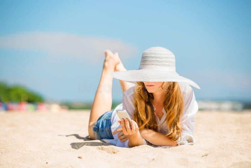 Mujer joven de Beautifil que miente en la playa en soleado fotografía de archivo