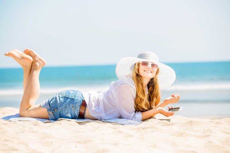 Mujer joven de Beautifil que miente en la playa en soleado imagenes de archivo