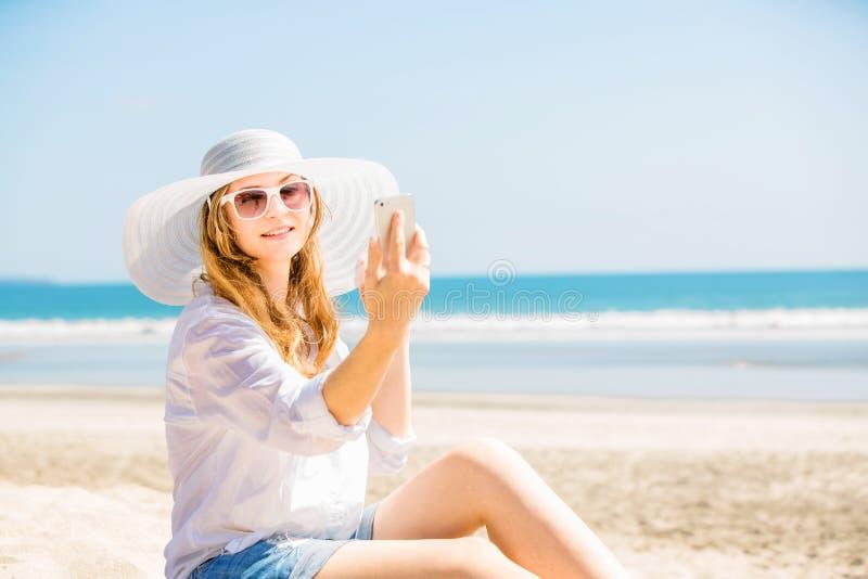 Mujer joven de Beautifil que se sienta en la playa en imagenes de archivo