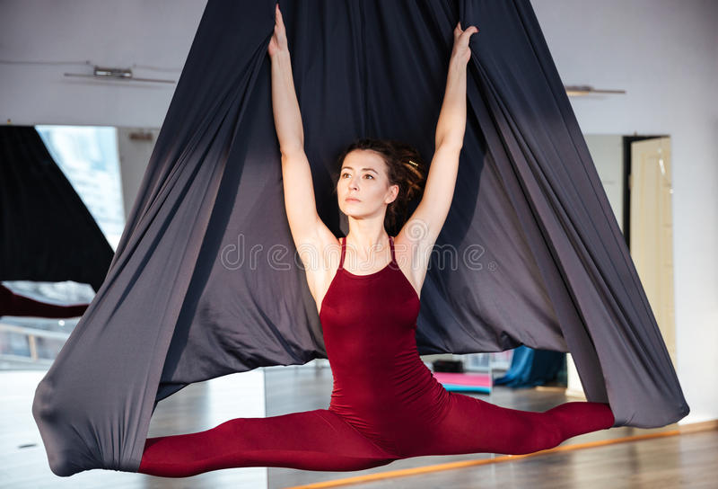 Mujer joven de Beautiul que hace yoga aérea en la hamaca negra imágenes de archivo libres de regalías