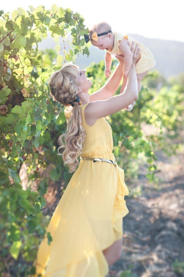 Mujer joven de Eautiful con una muchacha del niño en el campo de uvas fotos de archivo