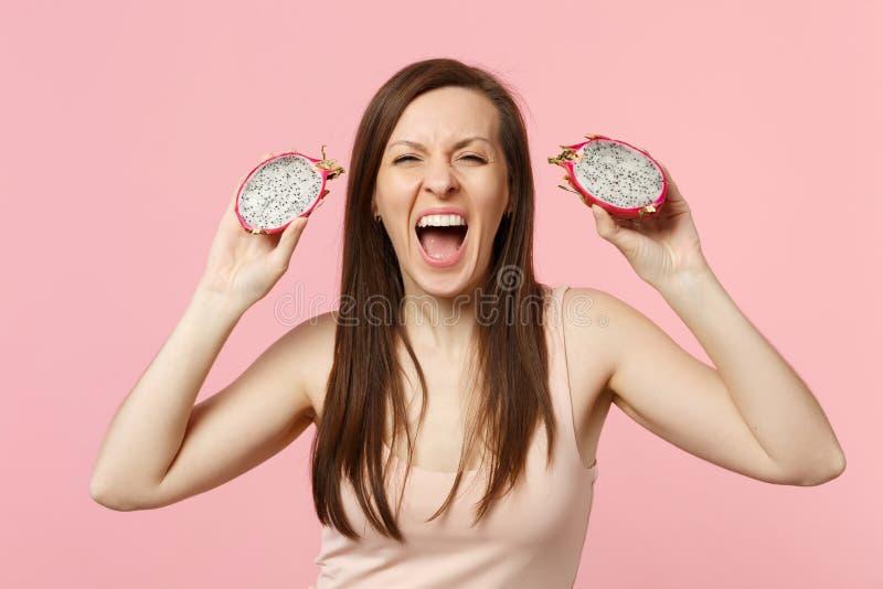 Mujer joven de griterío loca que sostiene dos halfs de pitahaya maduro fresco, fruta del dragón aislada en la pared en colores pa fotografía de archivo libre de regalías