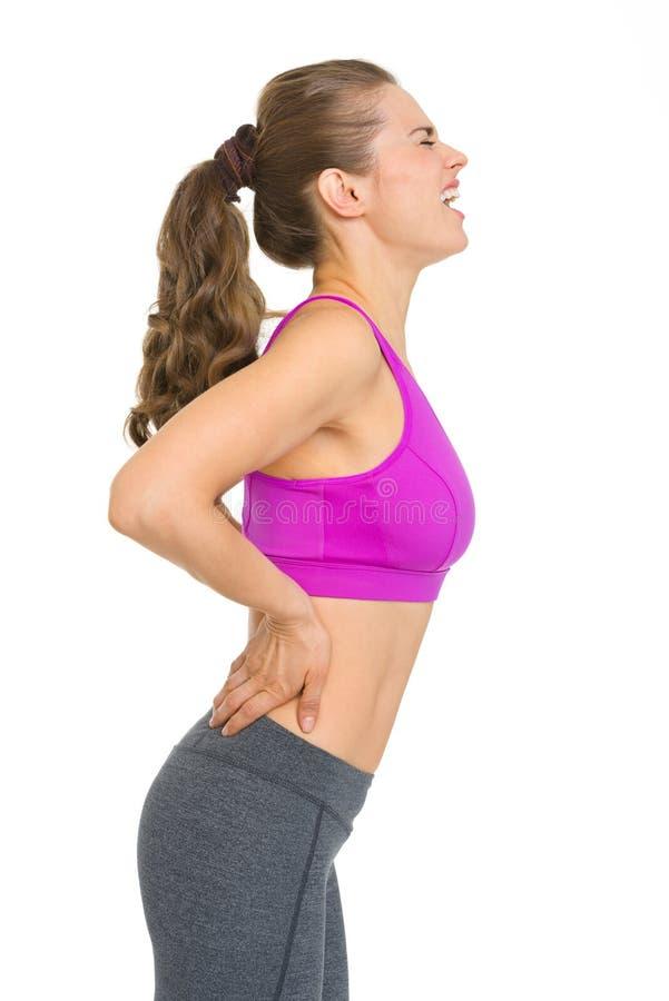Mujer joven de la aptitud con dolor de espalda imagen de archivo libre de regalías