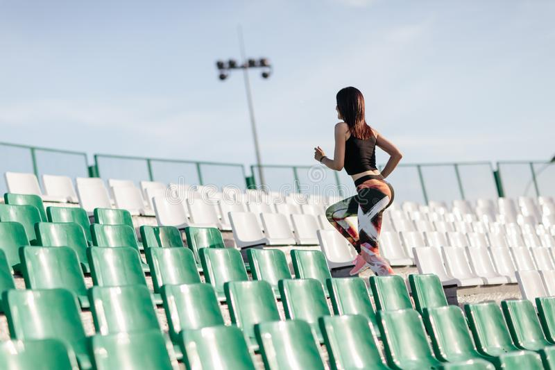 Mujer joven de la aptitud con una figura de los deportes en polainas y el funcionamiento superior negro para arriba en las escale fotografía de archivo