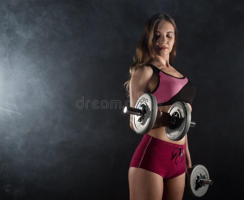 Mujer joven de la aptitud en el entrenamiento con pesas de gimnasia, morenita femenina muscular deportiva en humo imagenes de archivo