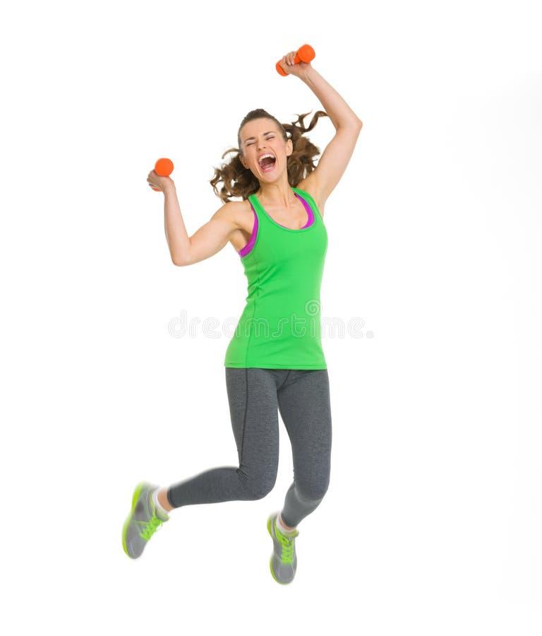 Mujer joven de la aptitud feliz con el salto de las pesas de gimnasia imagenes de archivo