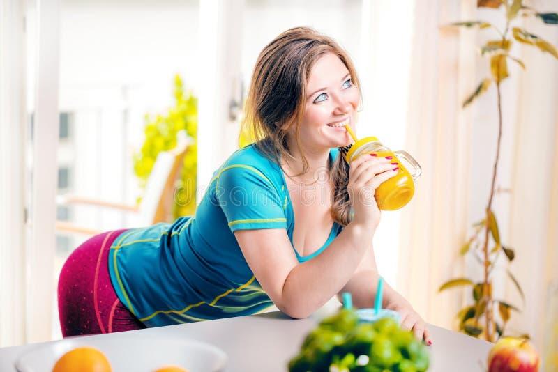 Mujer joven de la aptitud que bebe el smoothie anaranjado en cocina fotos de archivo libres de regalías