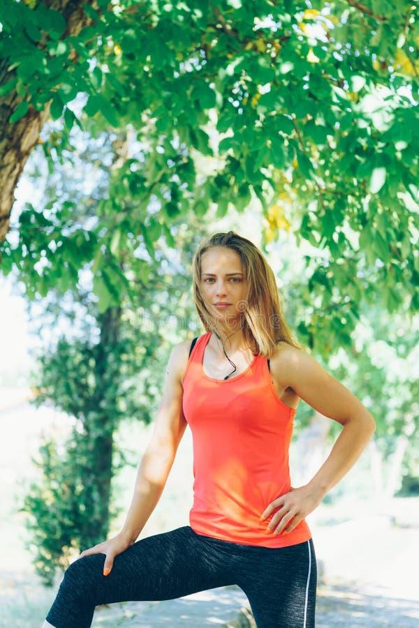 Mujer joven de la aptitud que ejercita en parque imagen de archivo