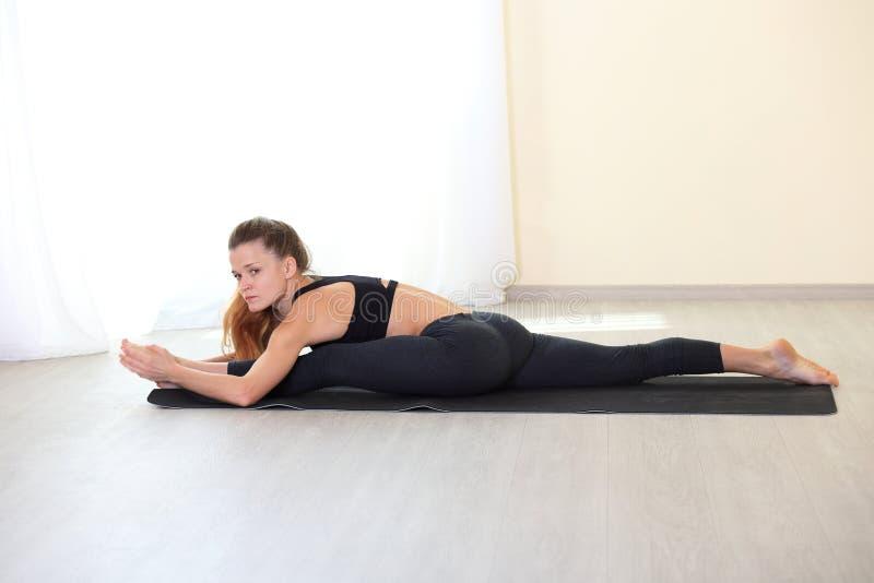 Mujer joven de la aptitud que estira en el gimnasio fotos de archivo