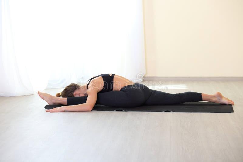 Mujer joven de la aptitud que hace el ejercicio de Pilates en el gimnasio foto de archivo