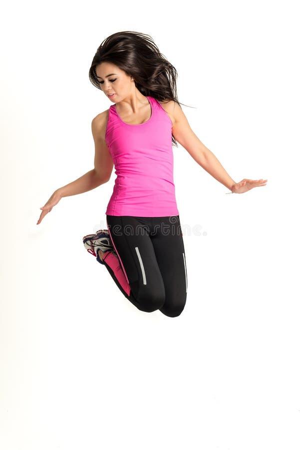 Mujer joven de la aptitud que salta arriba imagen de archivo