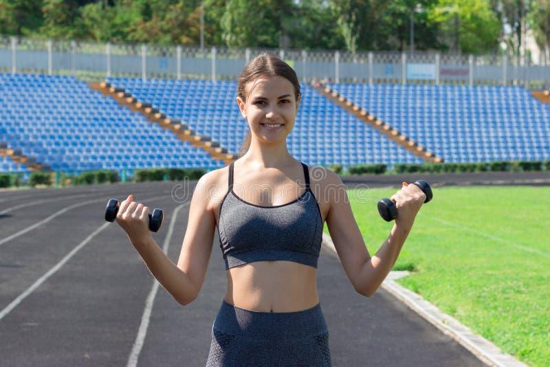 Mujer joven de la aptitud que se resuelve con pesas de gimnasia en los deportes del estadio y el concepto sano foto de archivo libre de regalías