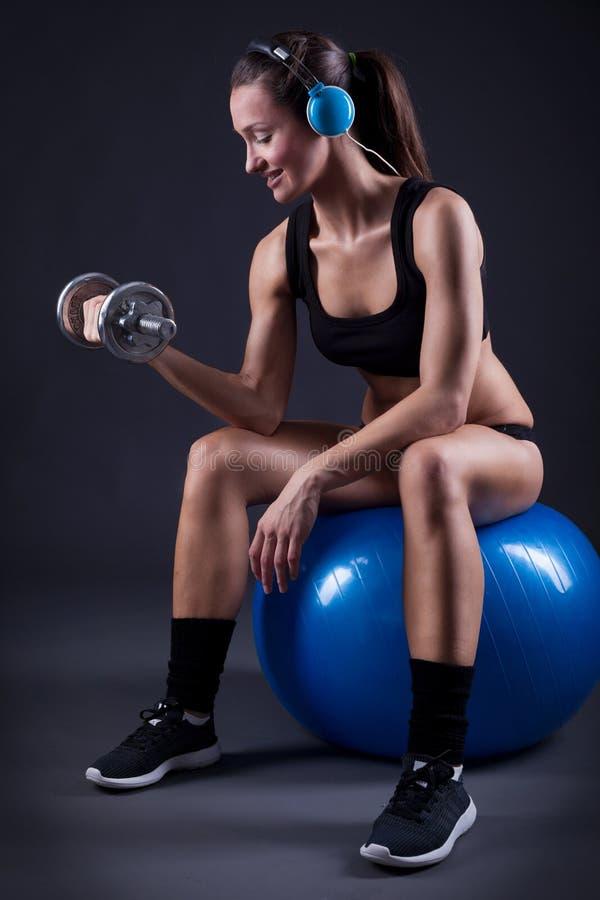 Mujer joven de la aptitud que se sienta en los pesos y el listeni de la elevación de la bola foto de archivo
