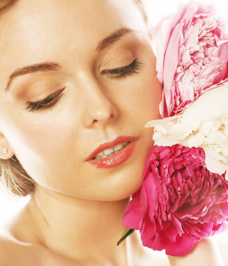 Mujer joven de la belleza con de la flor de la peonía del rosa del primer del maquillaje mirada apacible de la oferta suavemente imagen de archivo libre de regalías