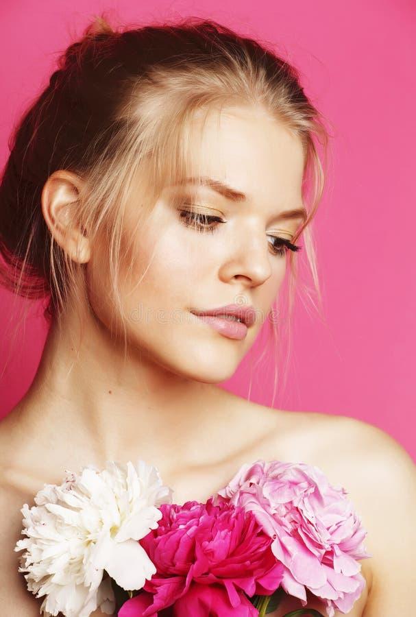Mujer joven de la belleza con de la flor de la peonía del rosa del primer del maquillaje mirada apacible de la oferta suavemente fotografía de archivo