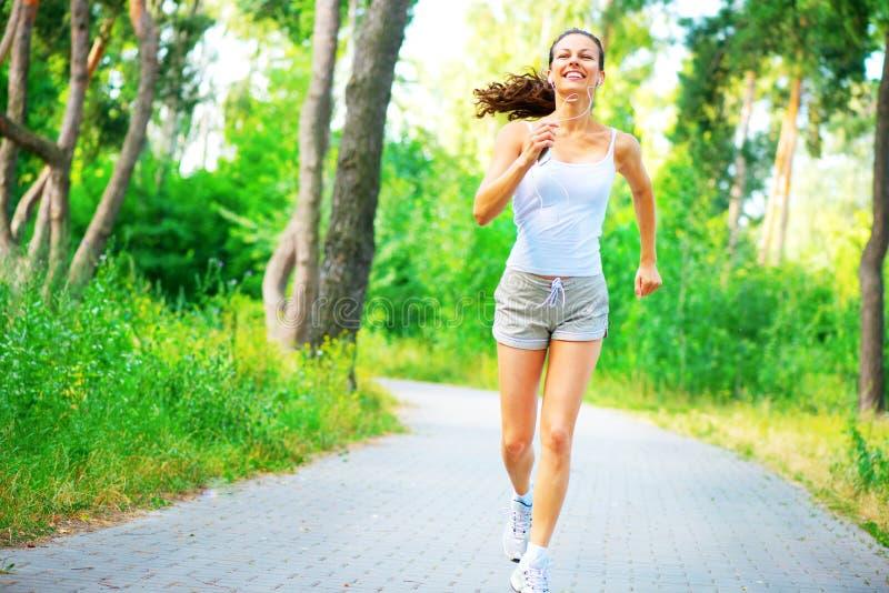 Mujer joven de la belleza con los auriculares que corren en el parque imágenes de archivo libres de regalías