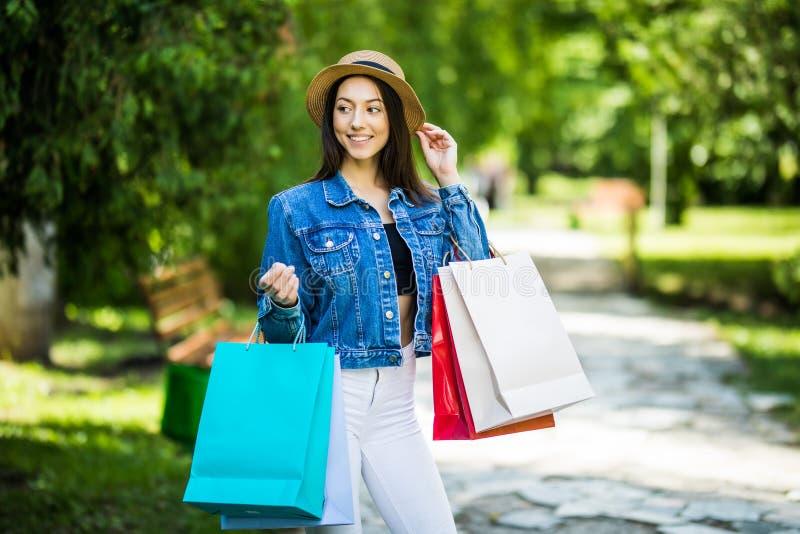 Mujer joven de la belleza con los bolsos de compras que camina en parque de la ciudad foto de archivo libre de regalías