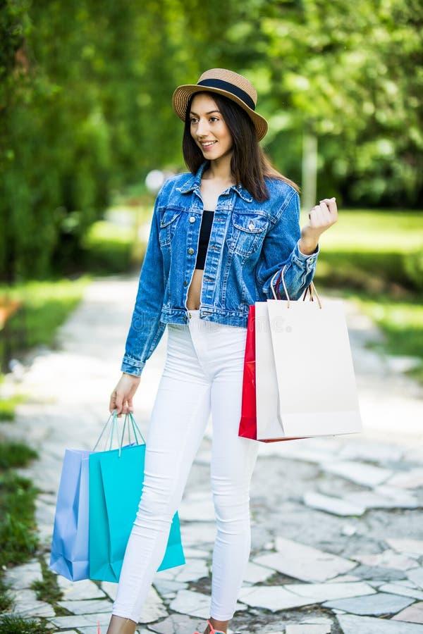 Mujer joven de la belleza con los bolsos de compras que camina en parque de la ciudad foto de archivo