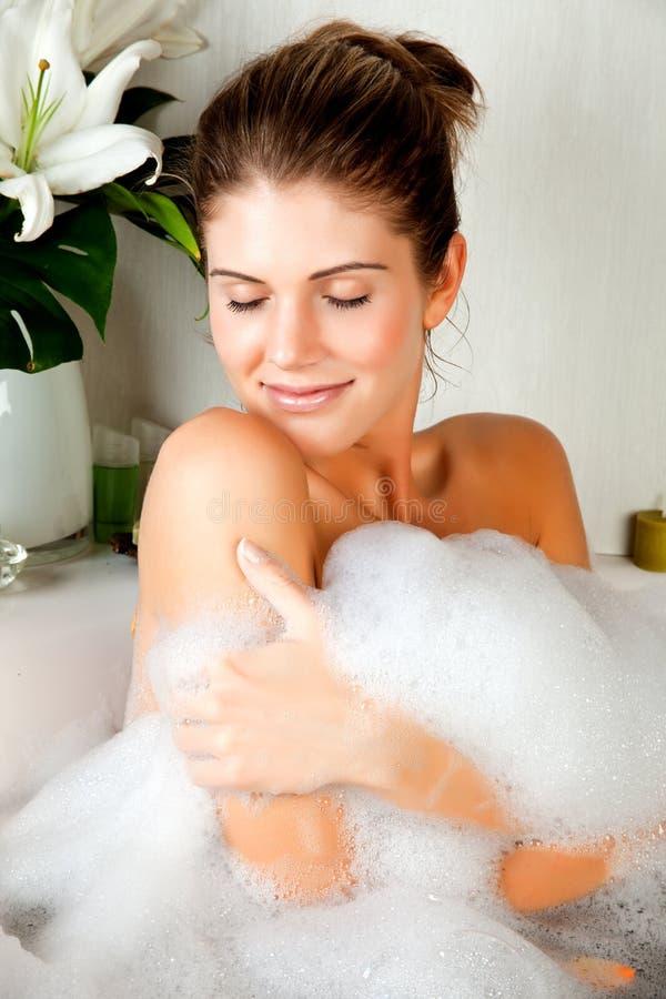 Mujer joven de la belleza en el baño que lava su carrocería fotografía de archivo libre de regalías