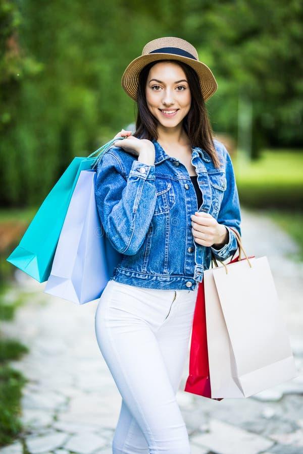Mujer joven de la belleza que sostiene los bolsos de compras que caminan en el par de la ciudad fotografía de archivo