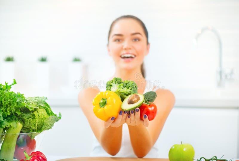 Mujer joven de la belleza que sostiene verduras frescas y las frutas en su cocina en casa imagenes de archivo