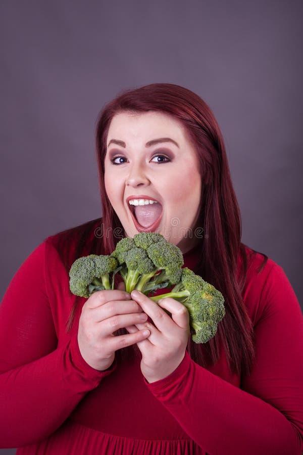 Mujer joven de la expresión emocionada que aviva hacia fuera los floretes del bróculi foto de archivo