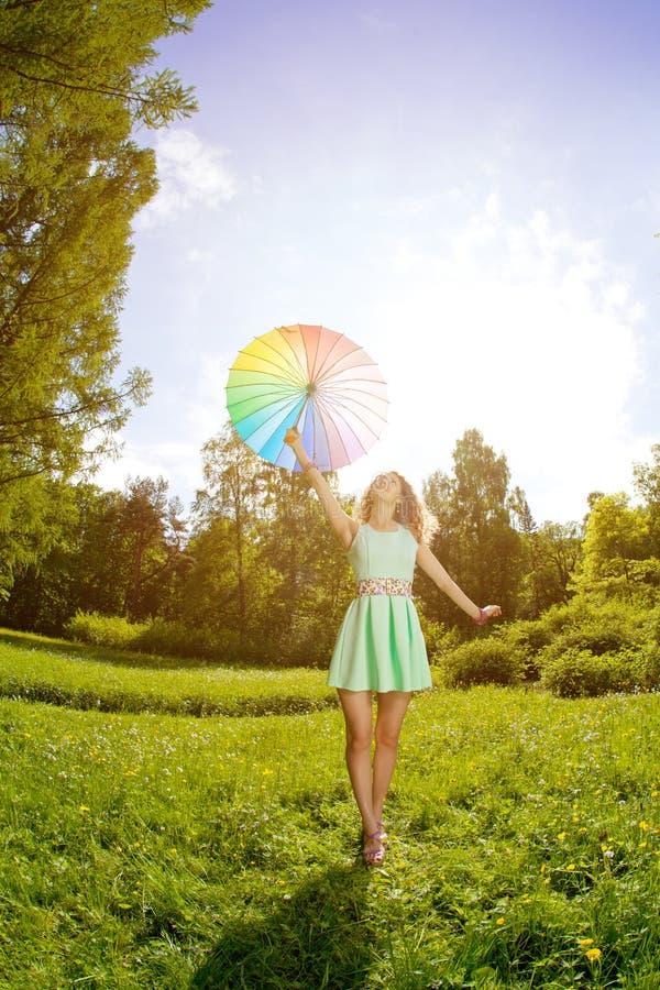 Mujer joven de la felicidad con el paraguas del arco iris foto de archivo
