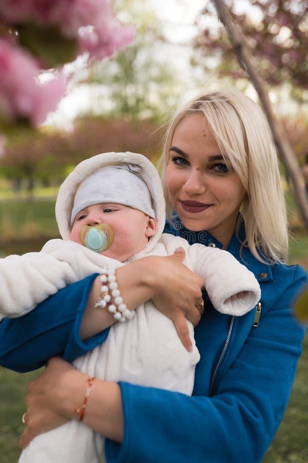 Mujer joven de la madre que disfruta del tiempo libre con su ni?o del beb? - ni?o blanco cauc?sico con la mano de un padre visibl foto de archivo libre de regalías
