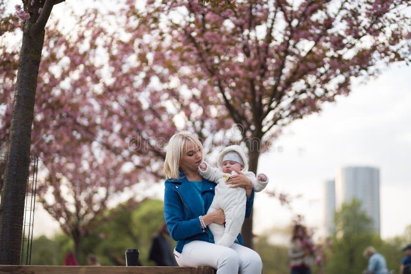Mujer joven de la madre que disfruta del tiempo libre con su ni?o del beb? - ni?o blanco cauc?sico con la mano de un padre visibl imagen de archivo