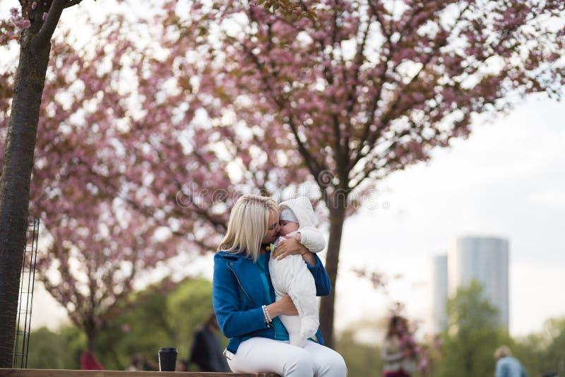 Mujer joven de la madre que disfruta del tiempo libre con su ni?o del beb? - ni?o blanco cauc?sico con la mano de un padre visibl fotografía de archivo