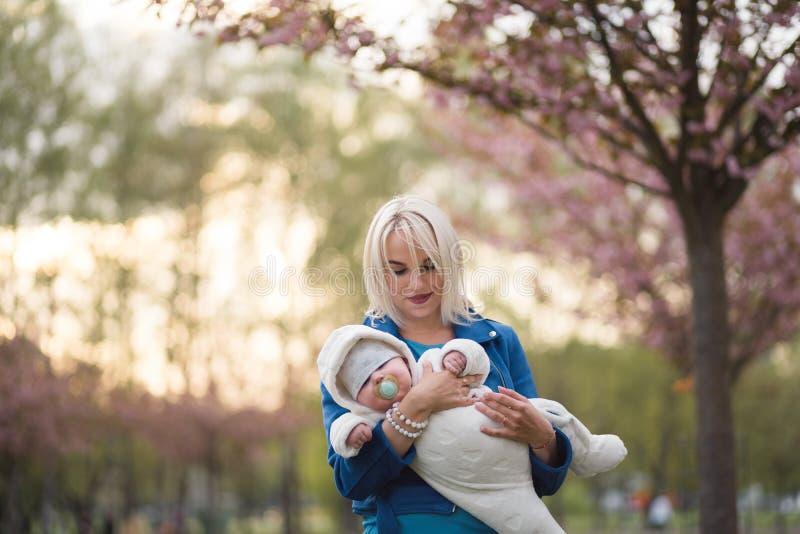 Mujer joven de la madre que disfruta del tiempo libre con su ni?o del beb? - ni?o blanco cauc?sico con la mano de un padre visibl fotografía de archivo libre de regalías
