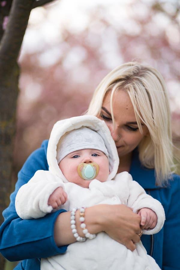 Mujer joven de la madre que disfruta del tiempo libre con su ni?o del beb? - ni?o blanco cauc?sico con la mano de un padre visibl foto de archivo