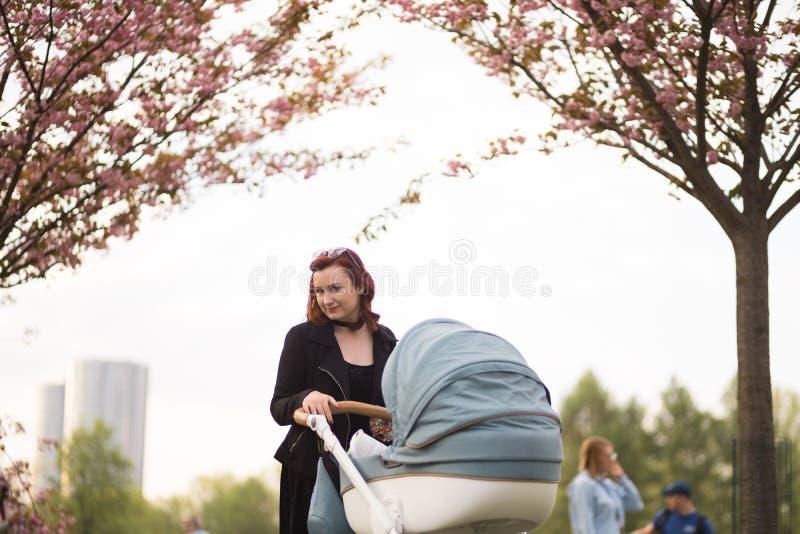 Mujer joven de la madre que disfruta del tiempo libre con su ni?o del beb? - ni?o blanco cauc?sico con la mano de un padre visibl fotos de archivo libres de regalías