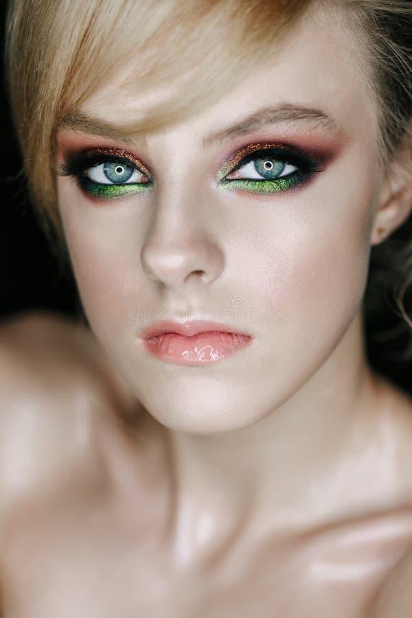 Mujer joven de la mirada seria con verde y los ojos de Brown imagen de archivo