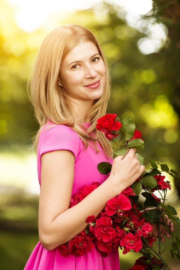Mujer joven de la moda de la primavera con las rosas en jardín de la primavera springti fotos de archivo libres de regalías